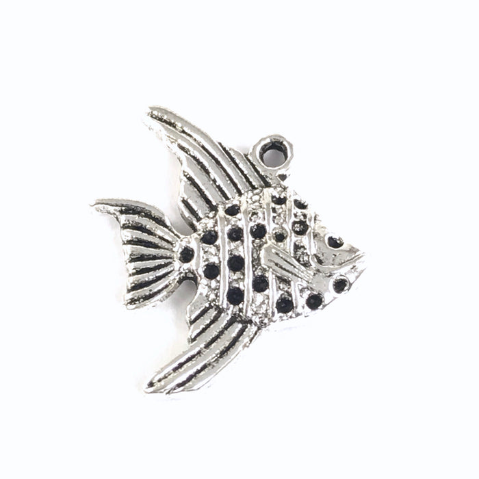 close up of a silver jewelry charm that looks like a fish