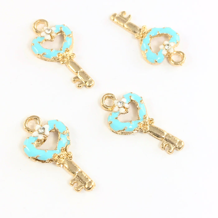 5 jewelry charms that are shaped like keys, blue and gold colour