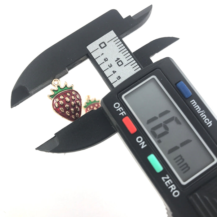 gold, red and green jewerly charms that look like strawberries, lenthwise on a digital ruler that reads 16.1