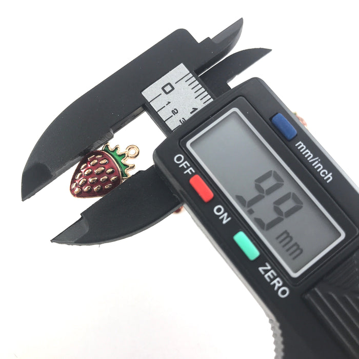 gold, red and green jewerly charms that look like strawberries, widthwise on a digital ruler that reads 9.9mm