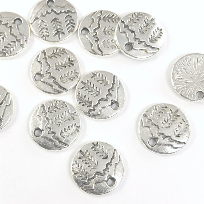 round silver jewerly charms with pine trees and mountains engraved on them