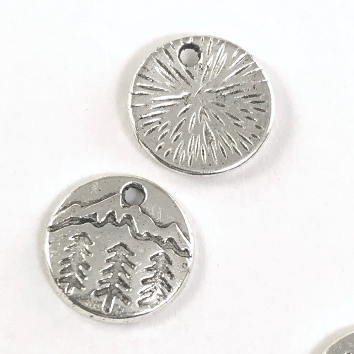 front and back of round silver jewelry charms with pine trees and mountains engraved on them
