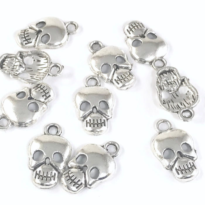 silver colour jewelry charms that look like skulls