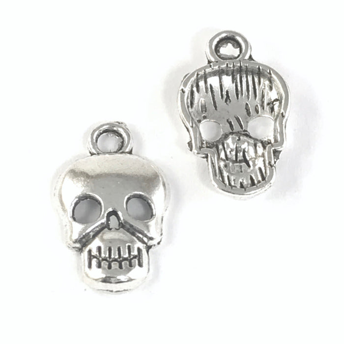 front and back of jewelry charms that look like skulls, silver in colour