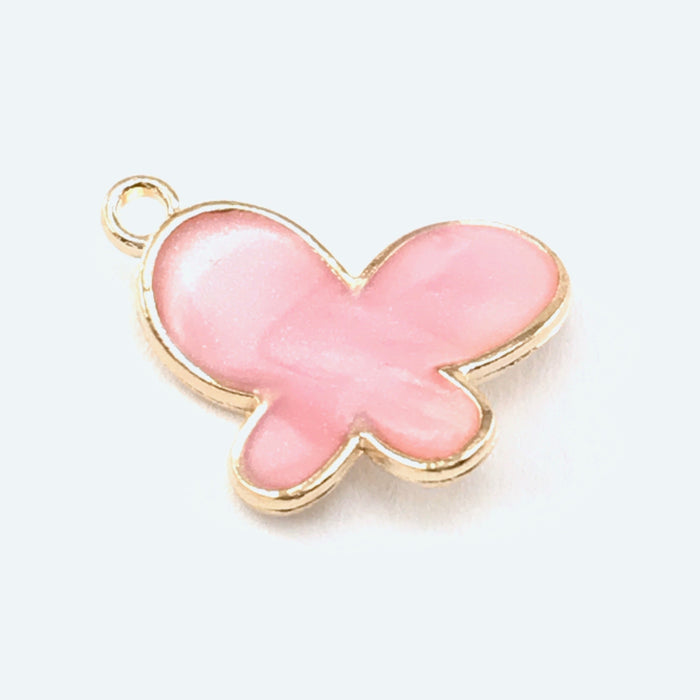 close up of a pink and gold jewelry charm shaped like a butterfly
