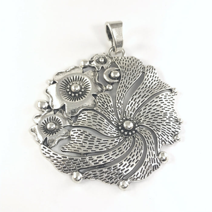 large silver jewerly pendant shaped like a flower