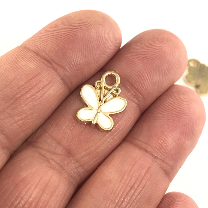 white and gold jewelry charm shaped like a butterfly sitting on a hand