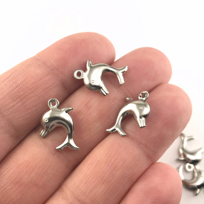 silver jewerly charms that look like dolphins, sitting on a hand