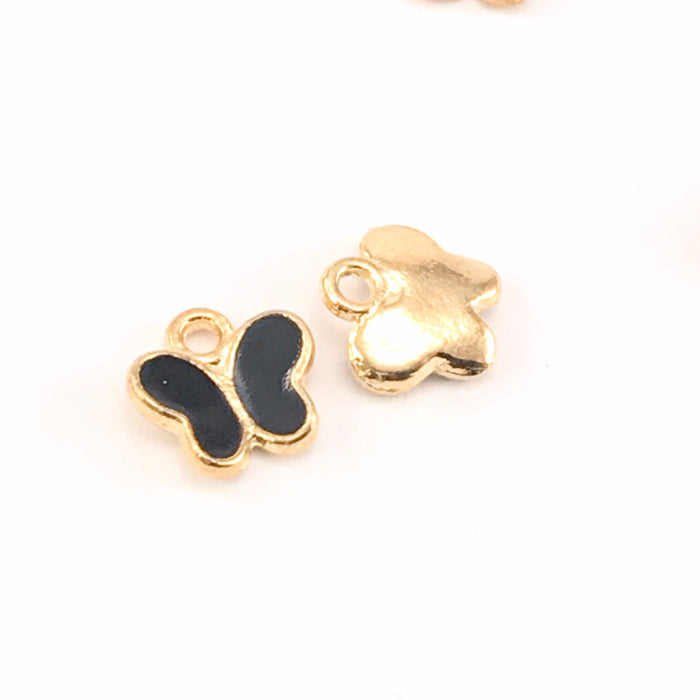 front and back of black and gold butterfly shaped charms