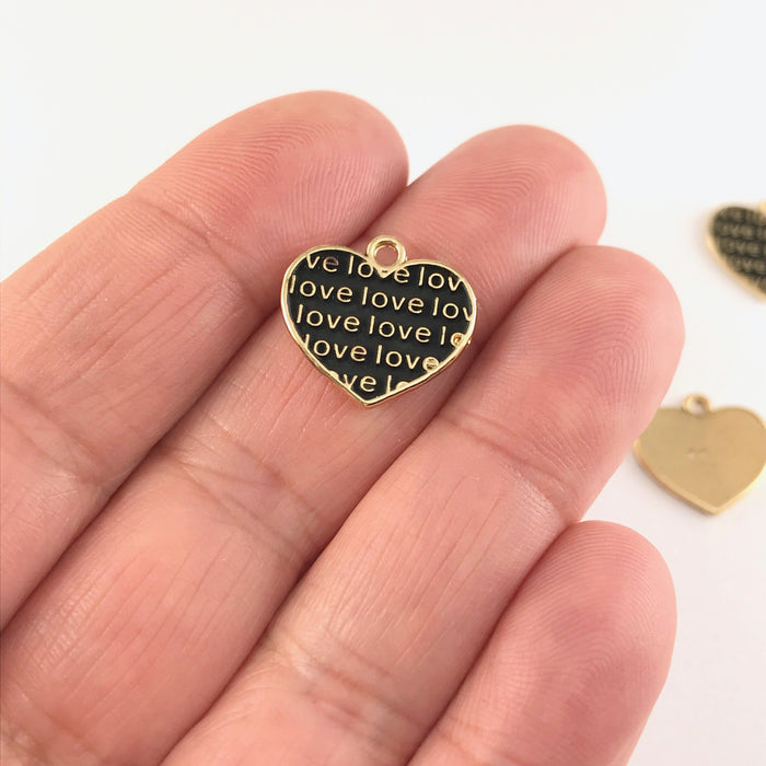 black and gold jewelry charms shaped like hearts with the word love on them, sitting on a hand