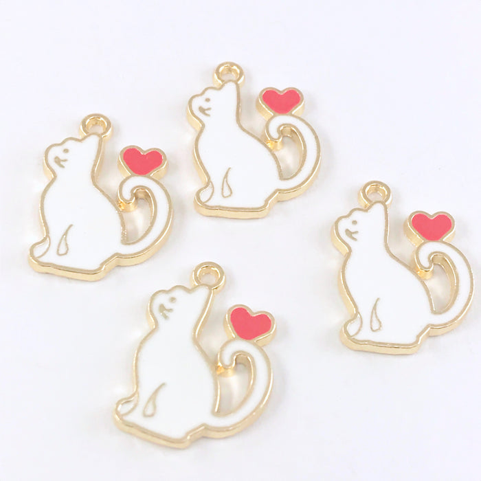 4 white and gold jewelry charms that are shaped like cats