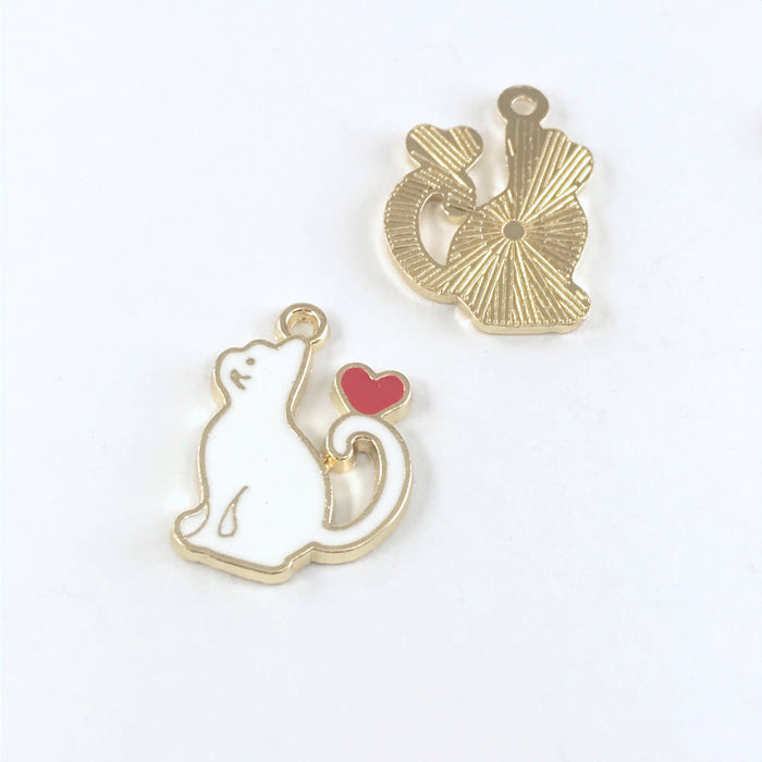 front and back of white and gold jewelry charms that are shaped like cats