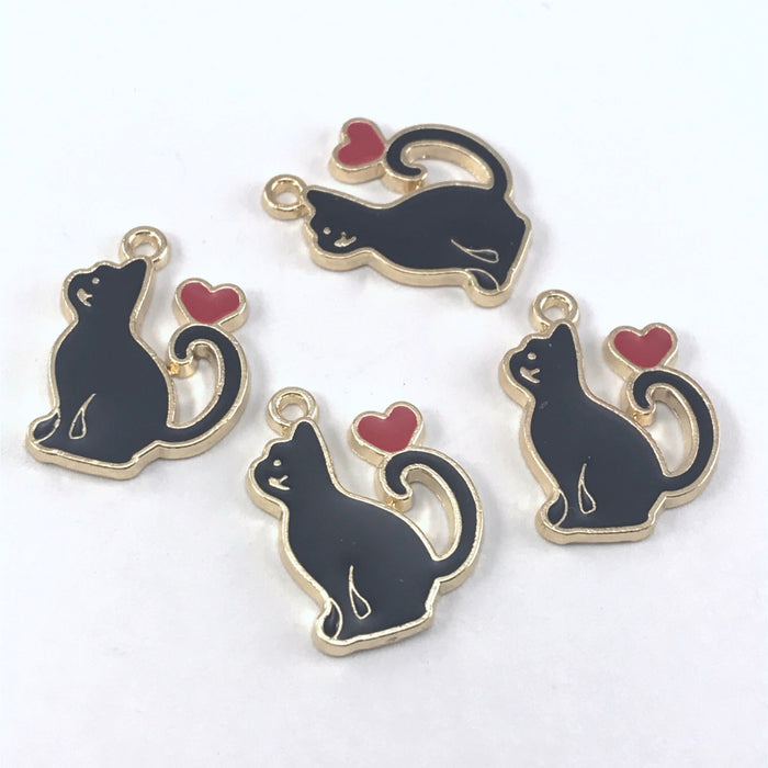 4 black and gold jewelry charms that are shaped like cats