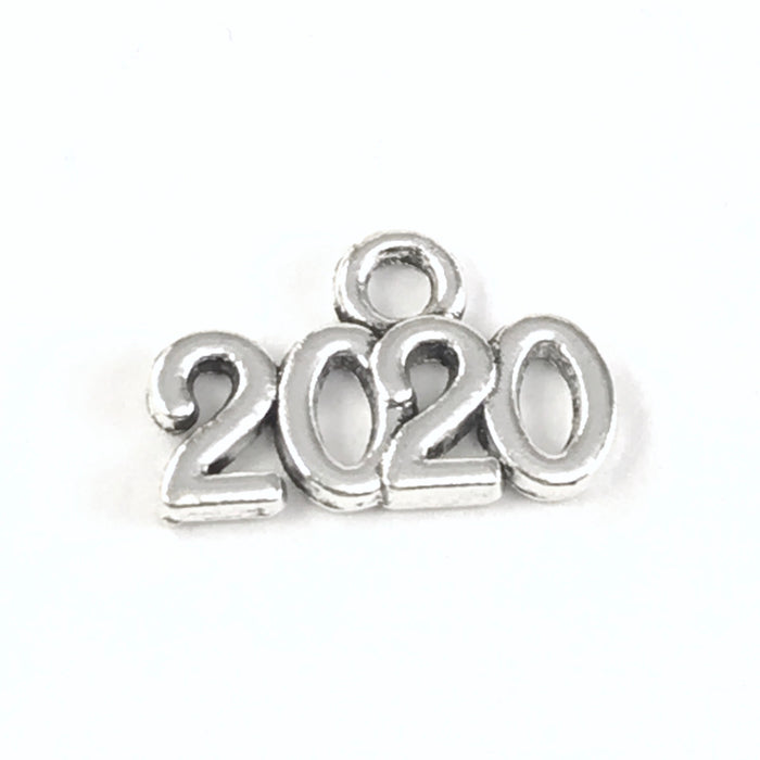 close up of a silver jewelry charm that says 2020