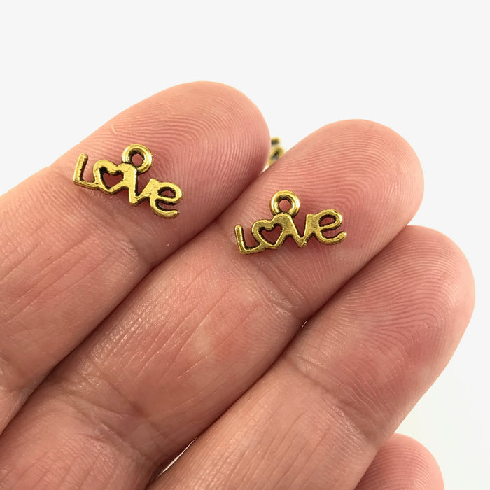 gold colour jewerly charms that say love, sitting on a hand