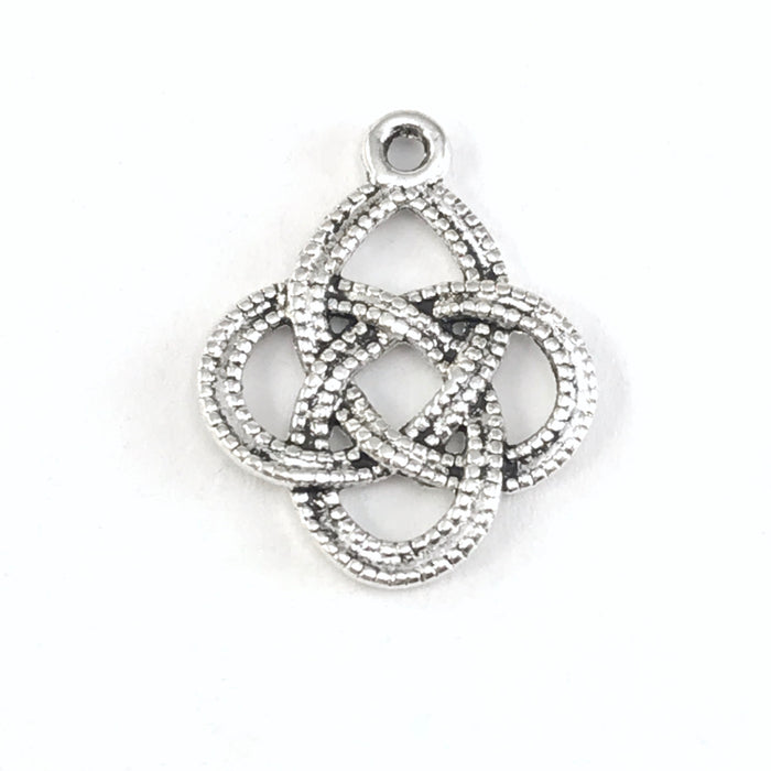 close up of silver colour jewerly charm shaped like celtic knot