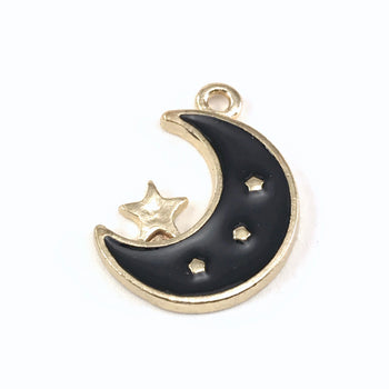 close up of a gold and black jewelry pendant shaped like a moon