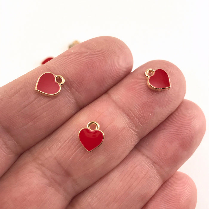 red and gold heart shaped jewelry charms sitting on a hand