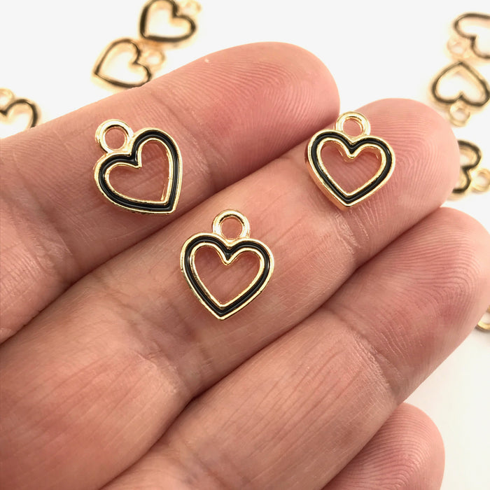 black and gold colour heart shaped jewelry charms sitting on a hand to show scale