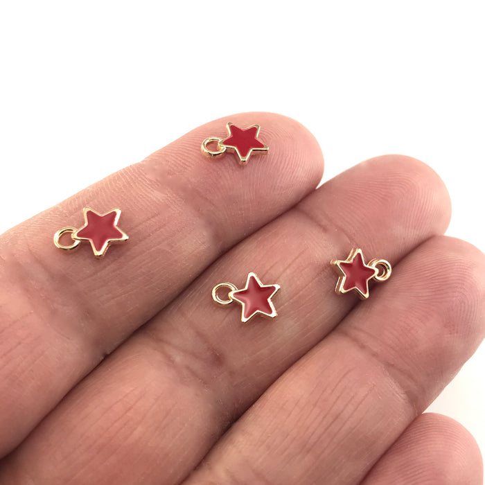 star shaped jewelry charms that are red and gold, sitting on a hand