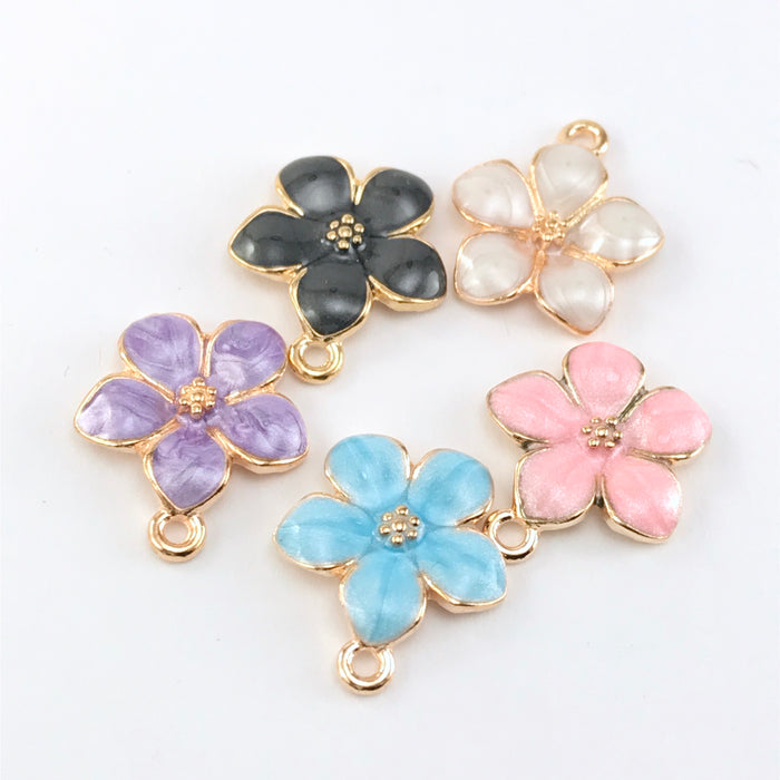 5 jewelry charms that are shaped like flowers and in purple, white, black, pink and blue colours.