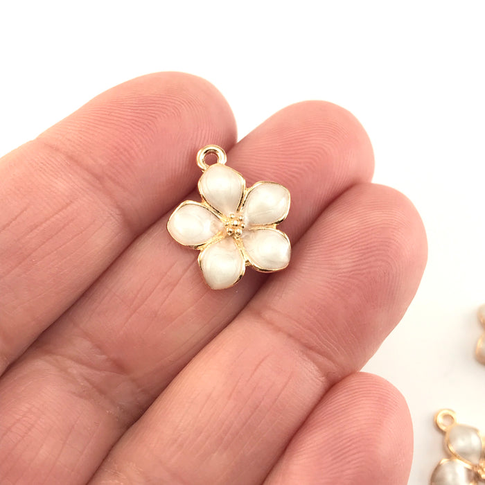 jewelry charm that looks like a white and gold flower, sitting on a hand
