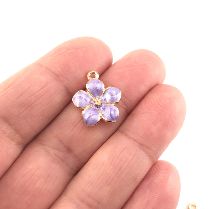 jewelry charms that look like purple and gold flowers, sitting on a hand