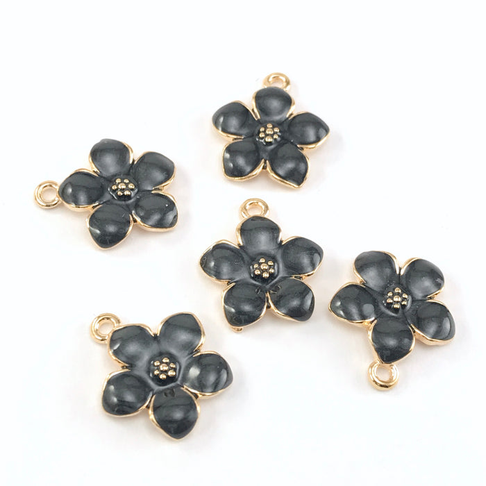 5 jewelry charms that look like black and gold flowers