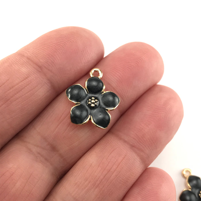 jewelry charms that look like black and gold flowers, sitting on a hand