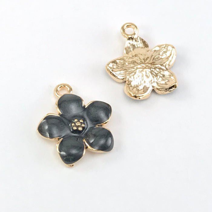 front and back of jewelry charms that look like black and gold flowers