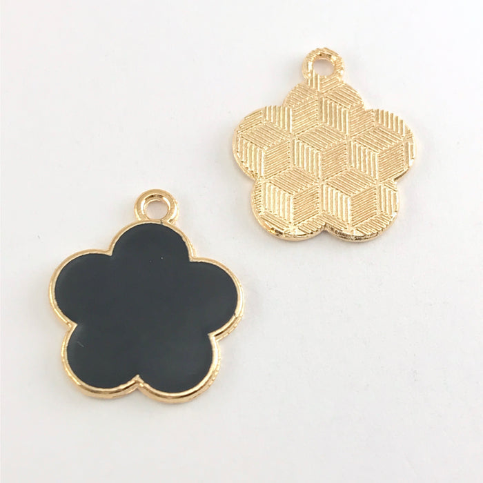 front and back of black and gold jewelry charm shaped like a flower, sitting on a hand