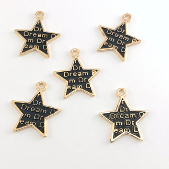 black and gold star shaped jewelry charms with the word dream on them