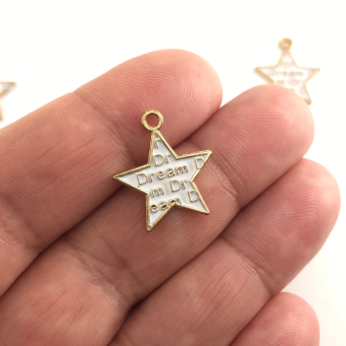 white and gold star shaped jewelry charms with the word dream on them, sitting on a hand