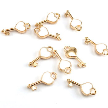 10 key shaped jewerly charms that are gold and white in colour