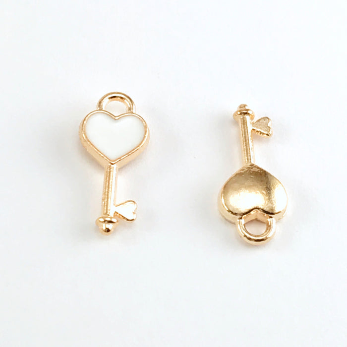 front and back of key shaped jewerly charms that are gold and white in colour
