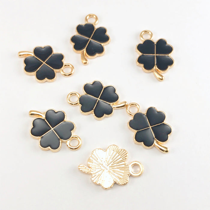 black and gold jewelry charms that look like four leaf clovers