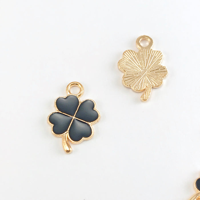 front and back of black and gold jewelry charms that look like four leaf clovers