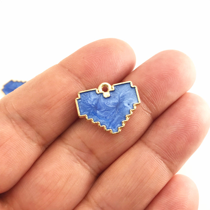 blue and gold jewerly pendants that are heart shaped, sitting on a hand to show scale