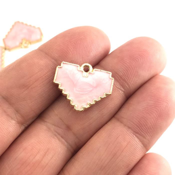 pink and gold jewelry pendants that are heart shaped sitting on a hand to show scale