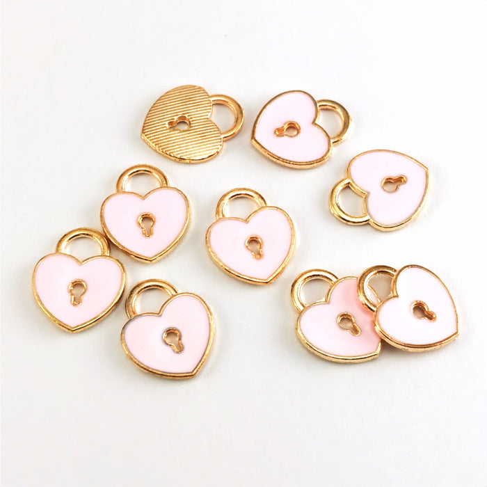10 pink and gold jewelry charms that are shpaed like hearts and have a key hole design in the middle