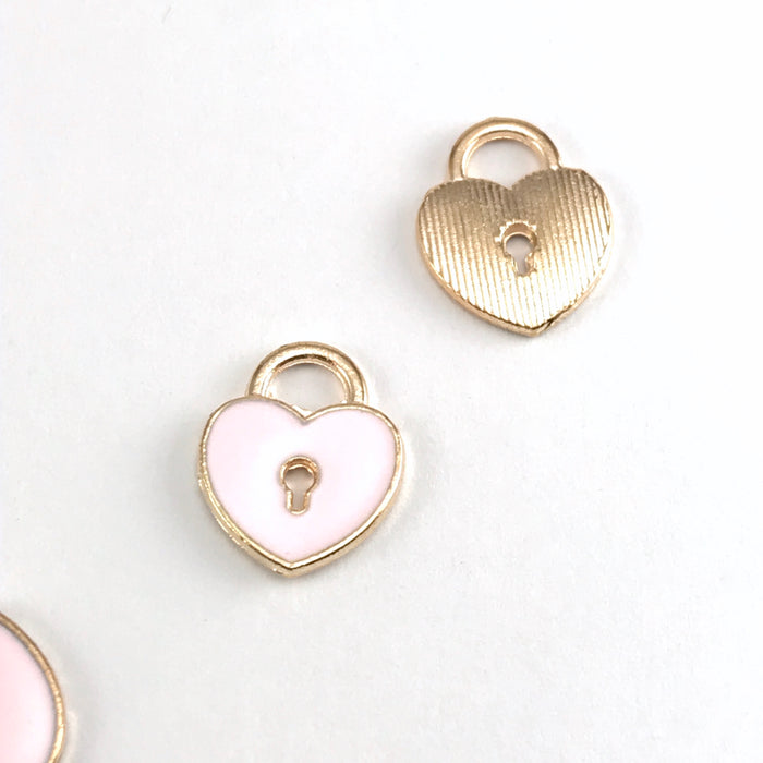front and back of pink and gold jewelry charms that are shpaed like hearts and have a key hole design in the middle