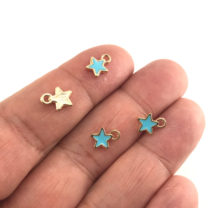 blue and gold colour jewelry charms shaped like stars, sitting on a hand to show scale