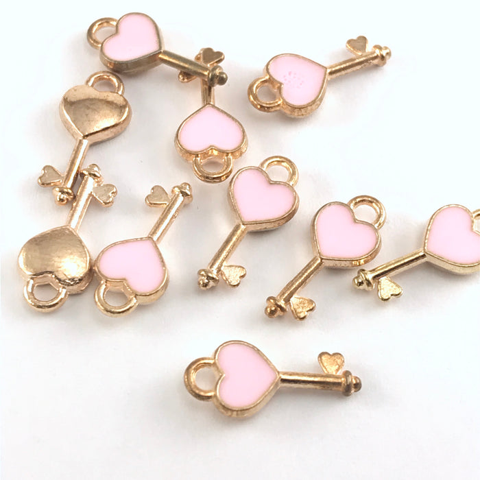 pink and gold jewelry charms shaped like keys