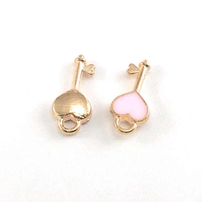 front and back of pink and gold jewelry charms shaped like keys