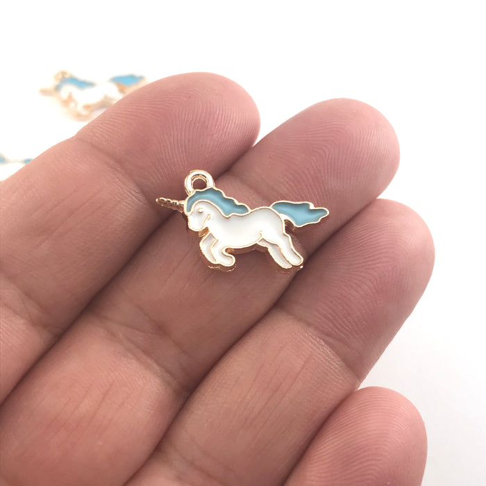 white blue and gold colour jewerly charm that looks lke a unicorn, sitting on a hand to show scale