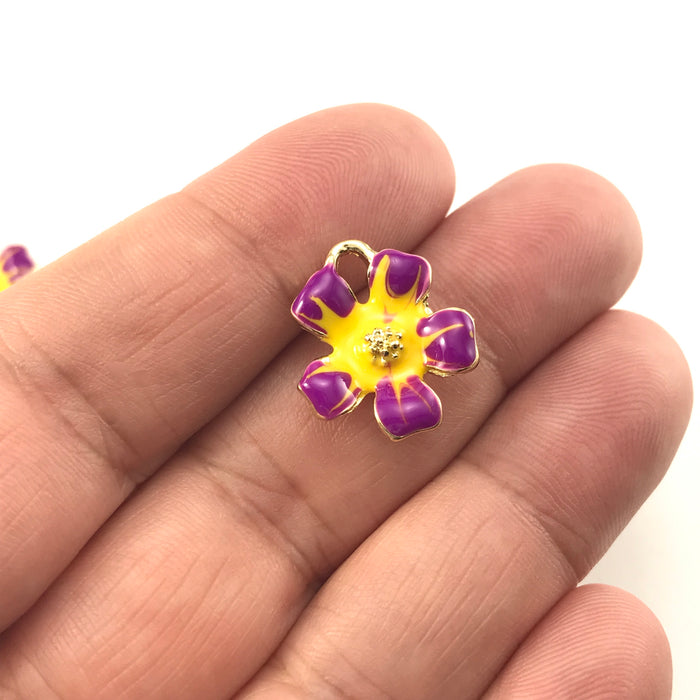 yellow, purple and gold colour jewerly charms shaped like flowers, sitting on a hand to show scale