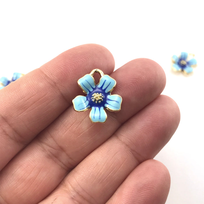 flower shaped jewelry charms that are gold, light blue and dark blue, sitting on a hand