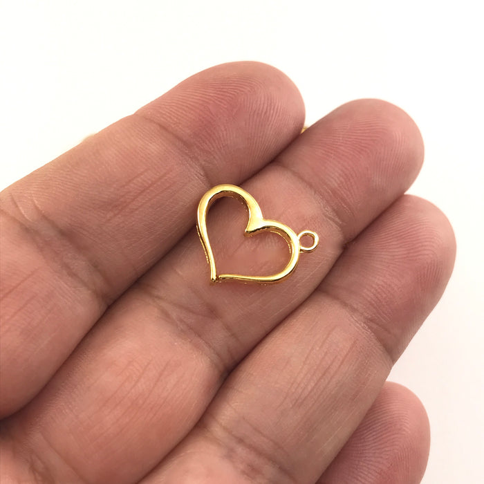 gold colour heart shaped jewerly charms sitting on a hand