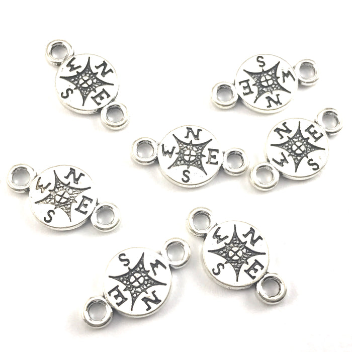 silver colour jewerly charms that look like compasses
