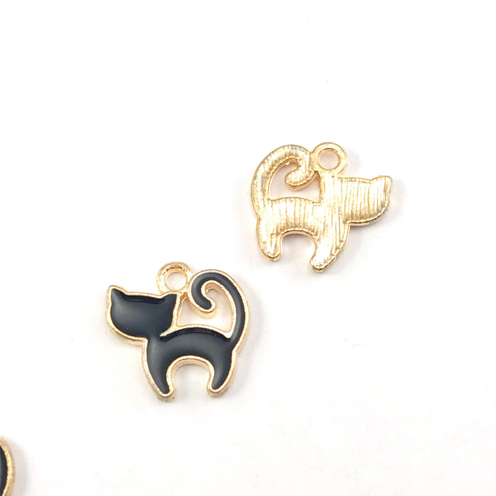 front and back of black and  gold colour jewerly charms that look like cats